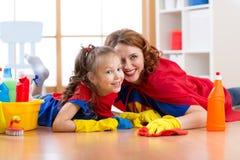 逗人喜爱的母亲和她的儿童女儿穿戴了象清洗地板和微笑的超级英雄 免版税库存图片