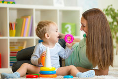 逗人喜爱的母亲和男婴一起演奏室内在 免版税库存图片