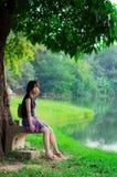 逗人喜爱的泰国女孩在河b附近单独坐 库存图片