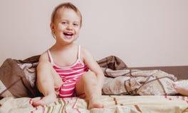 逗人喜爱的活跃小孩女孩滑稽的表示获得乐趣在床,并且不想要去睡着 免版税库存照片
