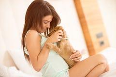 逗人喜爱的浅黑肤色的男人在与她的小狗宠物的床上 图库摄影