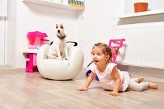 逗人喜爱的淘气女孩和一条幼小狗养殖教区牧师罗素狗 库存图片