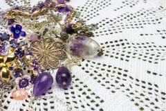逗人喜爱的淡紫色自然紫色的小珠、石头、水晶和项链在钩针编织小垫布 库存照片