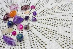 逗人喜爱的淡紫色自然紫色的小珠,石头,在钩针编织小垫布的水晶 库存图片