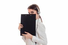 逗人喜爱的深色的妇女工作在与耳机的电话中心的和话筒掩藏她的在被隔绝的黑板后的微笑  免版税库存照片