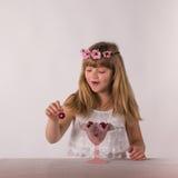 逗人喜爱的深色的小女孩高兴地吃大樱桃 免版税库存照片
