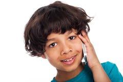 逗人喜爱的混合的族种谈话在手机。 免版税库存图片