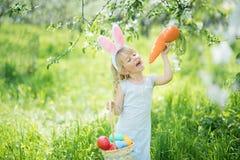逗人喜爱的滑稽的女孩用复活节彩蛋和兔宝宝耳朵在庭院 2个所有时段小鸡概念复活节彩蛋开花草被绘的被安置的年轻人 库存照片
