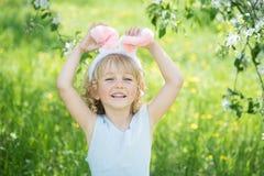 逗人喜爱的滑稽的女孩用复活节彩蛋和兔宝宝耳朵在庭院 2个所有时段小鸡概念复活节彩蛋开花草被绘的被安置的年轻人 免版税库存照片