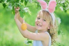 逗人喜爱的滑稽的女孩用复活节彩蛋和兔宝宝耳朵在庭院 2个所有时段小鸡概念复活节彩蛋开花草被绘的被安置的年轻人 库存图片