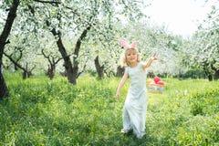 逗人喜爱的滑稽的女孩用复活节彩蛋和兔宝宝耳朵在庭院 2个所有时段小鸡概念复活节彩蛋开花草被绘的被安置的年轻人 图库摄影