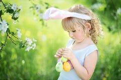 逗人喜爱的滑稽的女孩用复活节彩蛋和兔宝宝耳朵在庭院 2个所有时段小鸡概念复活节彩蛋开花草被绘的被安置的年轻人 免版税库存图片