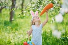逗人喜爱的滑稽的女孩用复活节彩蛋和兔宝宝耳朵在庭院 2个所有时段小鸡概念复活节彩蛋开花草被绘的被安置的年轻人 复活节彩蛋狩猎的笑的孩子 免版税库存图片