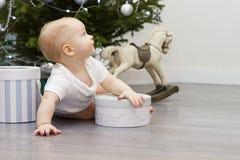 逗人喜爱的滑稽的男孩在预期奇迹的圣诞树下 免版税库存照片