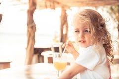 逗人喜爱的漂亮的孩子女孩在调查距离的热的夏日喜欢喝新鲜的汁液在夏天海滩假日期间与 免版税图库摄影