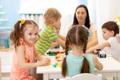 逗人喜爱的演奏教育玩具的妇女和孩子在幼儿园或托儿所室 免版税库存照片