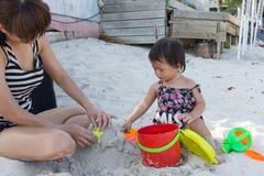 逗人喜爱的演奏沙子的女婴和美丽的母亲戏弄 免版税库存照片