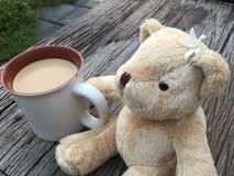 逗人喜爱的熊玩偶用早晨牛奶咖啡 免版税库存照片