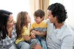 逗人喜爱的父项兄弟坐他们的沙发 免版税图库摄影