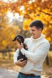 逗人喜爱的狗和他的所有者获得乐趣在公园 免版税库存图片