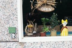 逗人喜爱的猫玩偶和打开木标志宽广通过杯商店窗口 库存图片