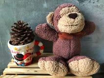 逗人喜爱的猴子微笑玩偶坐木箱有水泥背景 免版税库存图片