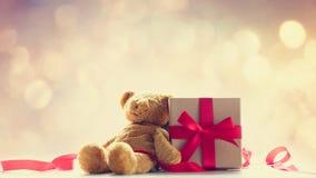 逗人喜爱的玩具熊、红色丝带和美丽的礼物在神仙的lig 图库摄影
