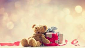 逗人喜爱的玩具熊、红色丝带和美丽的礼物在神仙的lig 库存照片