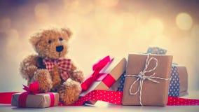 逗人喜爱的玩具熊、红色丝带和美丽的礼物在神仙的lig 免版税库存图片