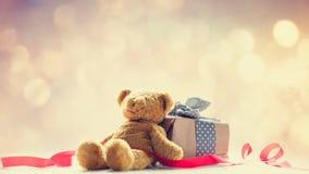 逗人喜爱的玩具熊、红色丝带和美丽的礼物在神仙的ligh 图库摄影