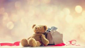 逗人喜爱的玩具熊、红色丝带和美丽的礼物在神仙的ligh 免版税图库摄影