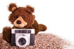 逗人喜爱的玩具熊是与在沙子的一台照相机 库存照片