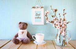 逗人喜爱的玩具熊,咖啡在春天樱桃树旁边的 库存图片