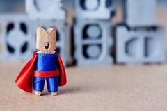 逗人喜爱的玩具特级英雄字符 在蓝色衣服和红色海角的晒衣夹 灰色积木背景 免版税库存图片