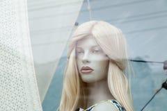逗人喜爱的现实女性白肤金发的时装模特面孔特写镜头在商店窗口里 免版税库存照片
