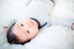 逗人喜爱的男婴在演播室射击 婴孩和家庭的时尚图象 可爱的婴孩在一张软的白色地毯躺下 图库摄影