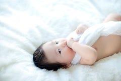 逗人喜爱的男婴在演播室射击 婴孩和家庭的时尚图象 可爱的婴孩在一张软的白色地毯躺下 免版税库存图片