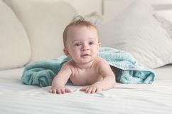 逗人喜爱的男婴被定调子的画象有说谎在床上的湿头发的以后有浴 库存照片