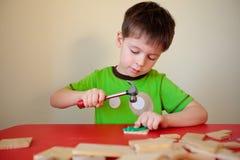 逗人喜爱的男孩与锤子和钉子一起使用 库存照片