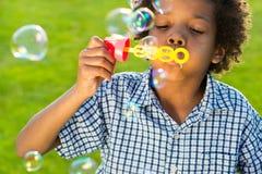 逗人喜爱的男孩做泡影 免版税图库摄影