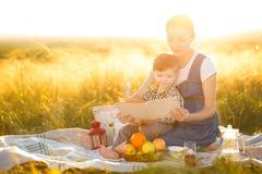 逗人喜爱的男孩儿子和他美丽的怀孕的母亲一顿野餐的在一个美好的秋天或夏日读了一本书 库存图片