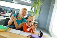 逗人喜爱的男孩和他的妈妈坐在办公室和举行铅笔的书桌 免版税库存照片
