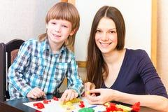逗人喜爱的男孩和他的母亲一起演奏五颜六色的戏剧面团 免版税库存图片