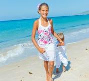 逗人喜爱的男孩和女孩海滩的 免版税库存图片