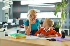 逗人喜爱的男孩和妇女坐在书桌在办公室 免版税库存图片