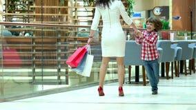 逗人喜爱的男孩和母亲有圣诞节礼物的在购物中心 家庭圣诞节购物 有获得的妈妈的孩子乐趣 股票录像