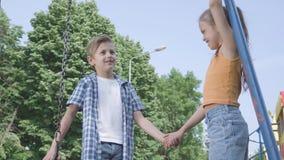 逗人喜爱的男孩和美女有长发的握手和谈话在摇摆附近,愉快地微笑 两三愉快 影视素材