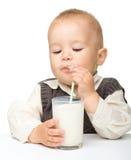 逗人喜爱的男孩喝少许牛奶 免版税库存图片