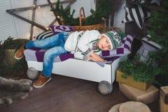 逗人喜爱的男孩在一张床上睡觉在一个装饰的演播室 免版税图库摄影