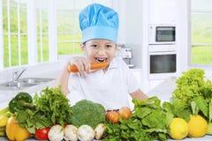 逗人喜爱的男孩在厨房里吃一棵红萝卜 免版税库存图片